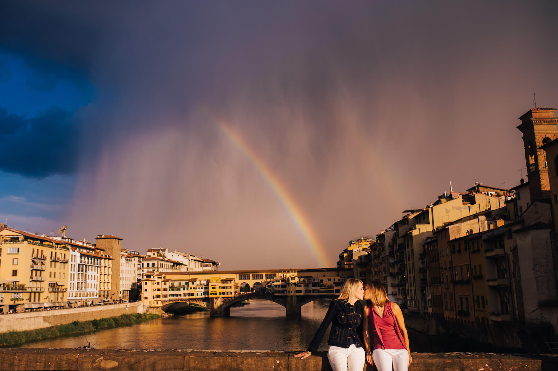 LGBTQ+ couple kissing while sitting on a bridge ledge together with a rainbow in the background in Florence, Italy