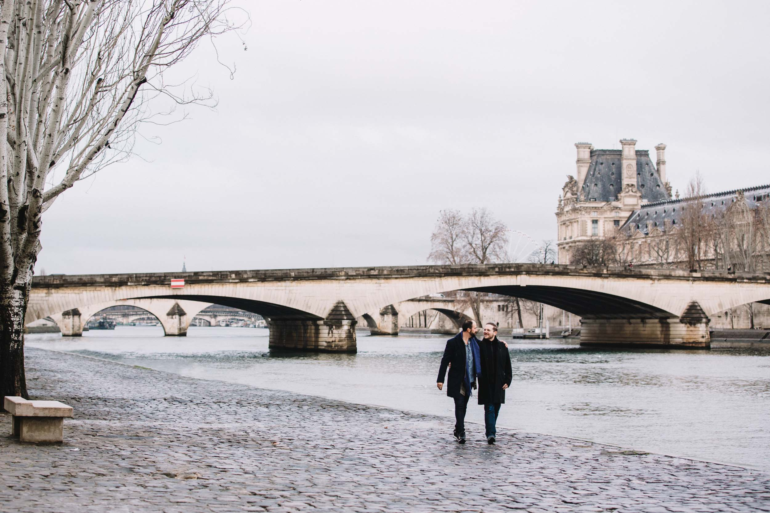 Couple hugging and walking along the Siene river together in Paris, France on a couples trip