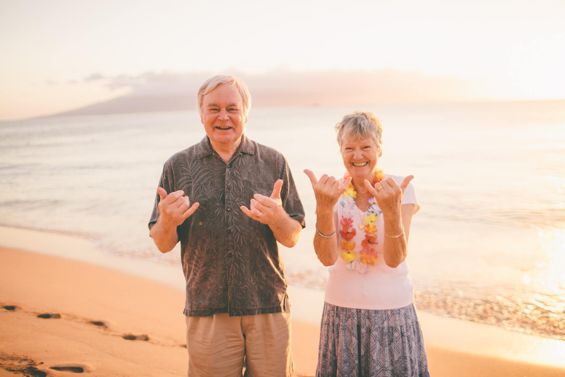 "Mature couple smiling and giving the ""Aloha"" hand sign with both hands in Maui, Hawaii USA"