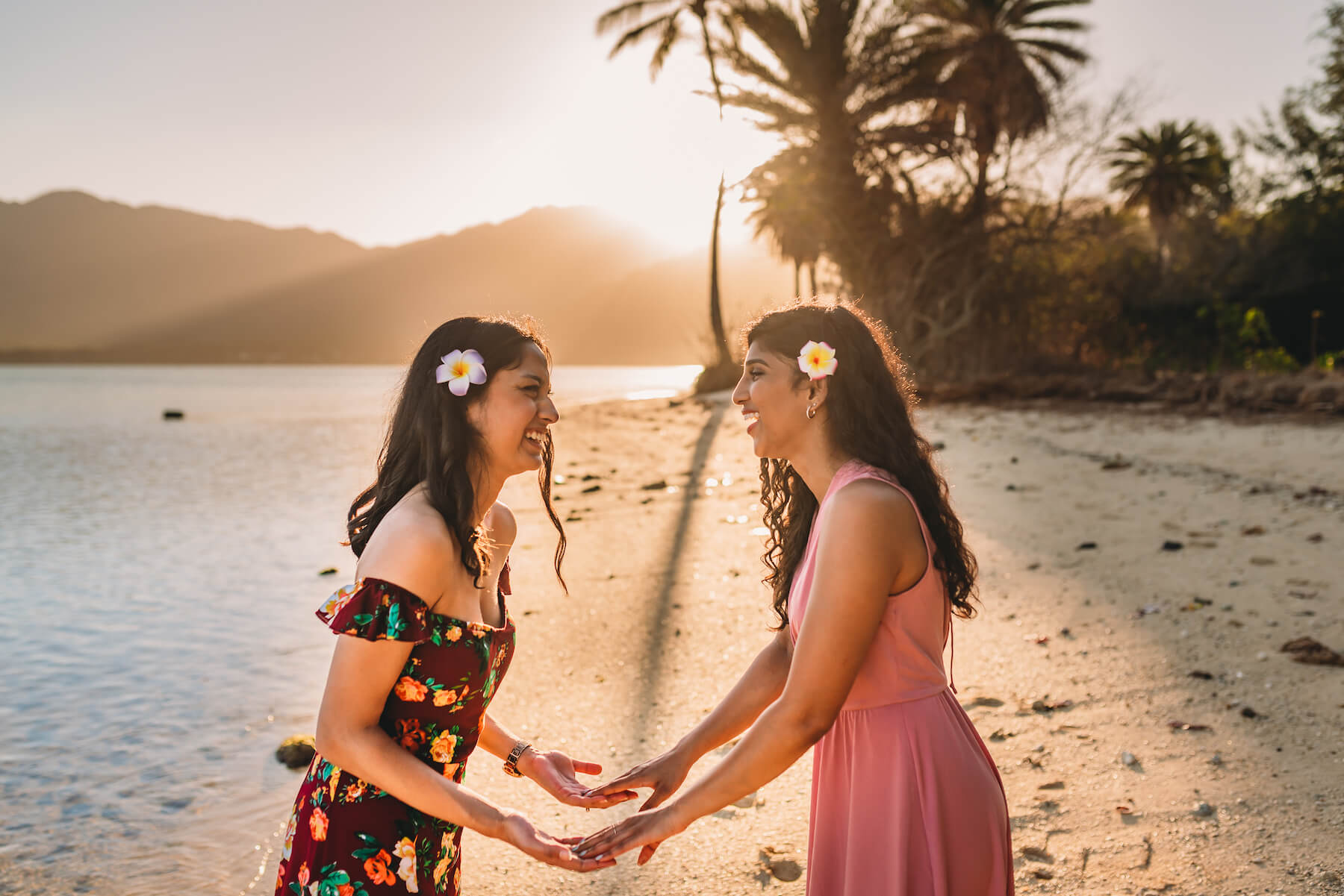 Two friends holding hands and looking at each other on Kualoa beach, Honolulu, Hawaii