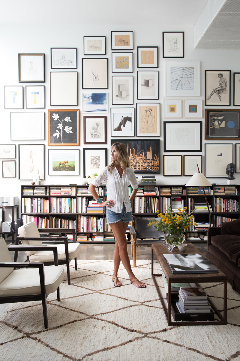 Woman standing in living room surrounded by artwork