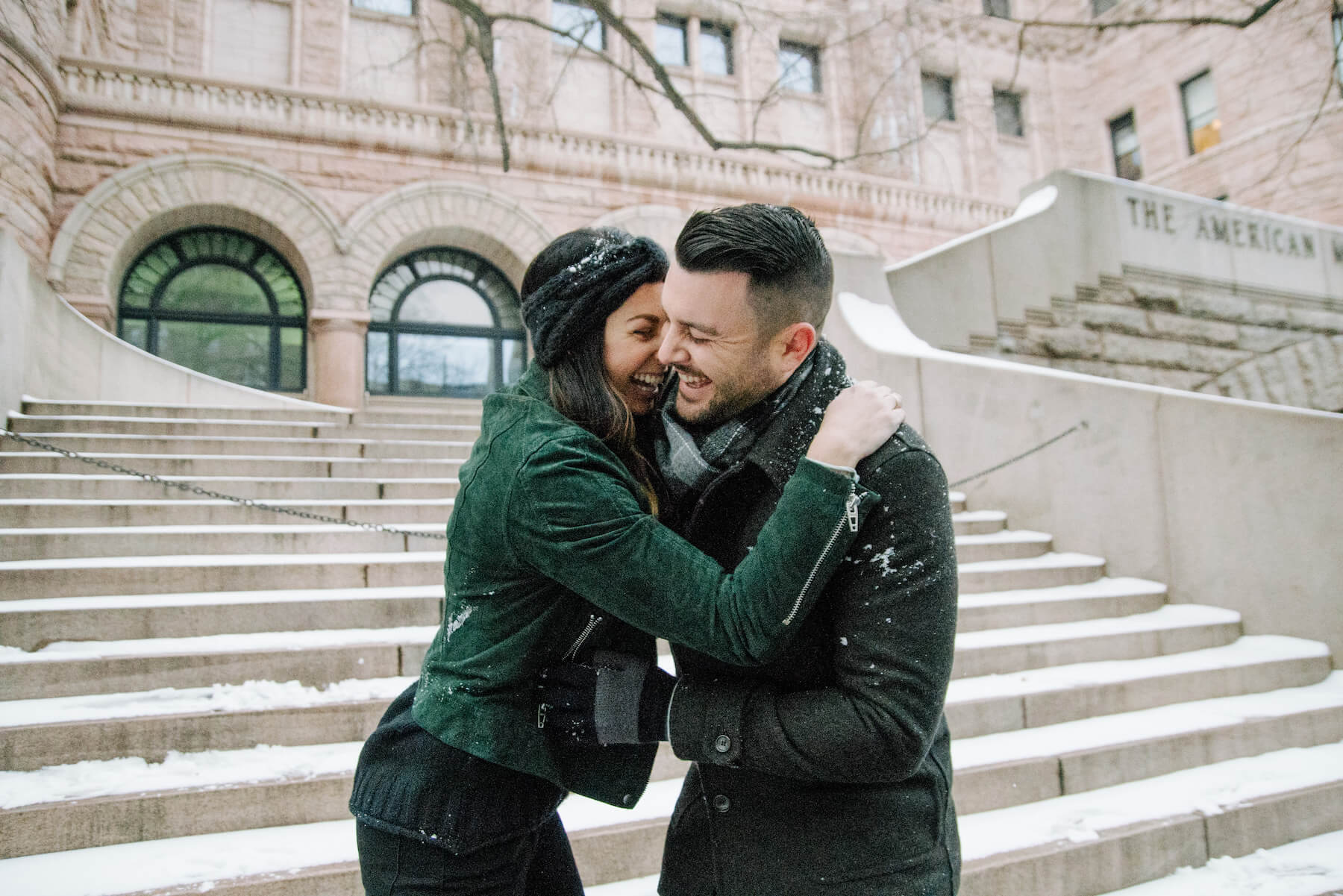 Couple laughing and holding each other in the snow in New York City, USA