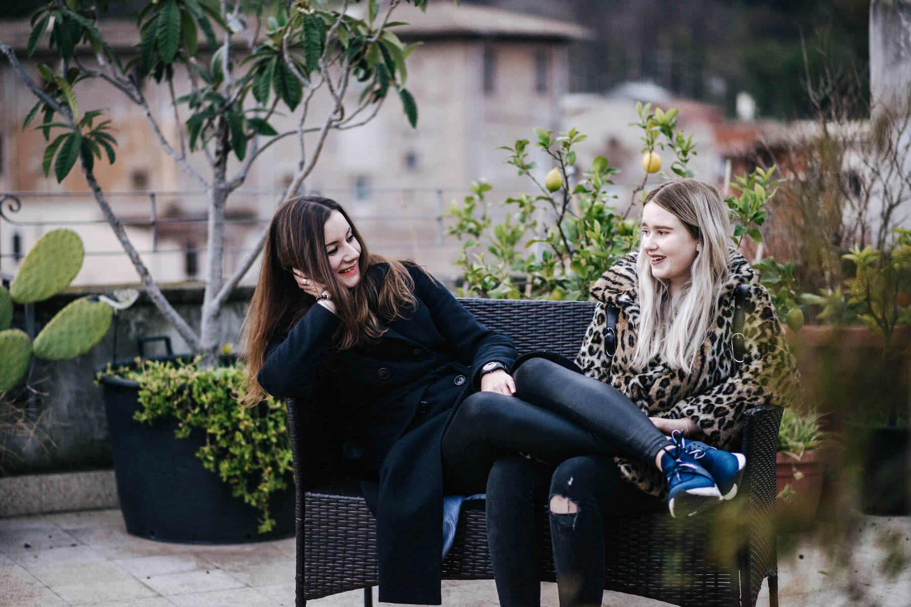 Sisters sitting on a bench together on a rooftop patio on a family trip in Rome, Italy