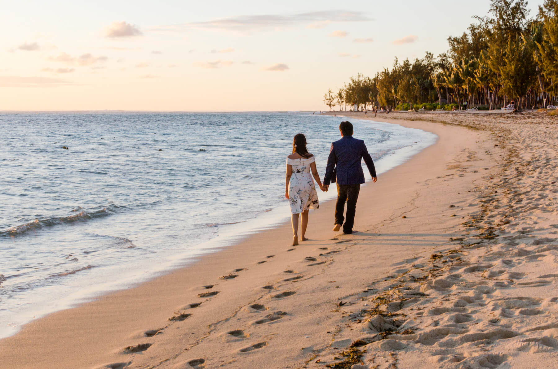 Couple holding hands and walking down the beach together at sunset in Mauritius