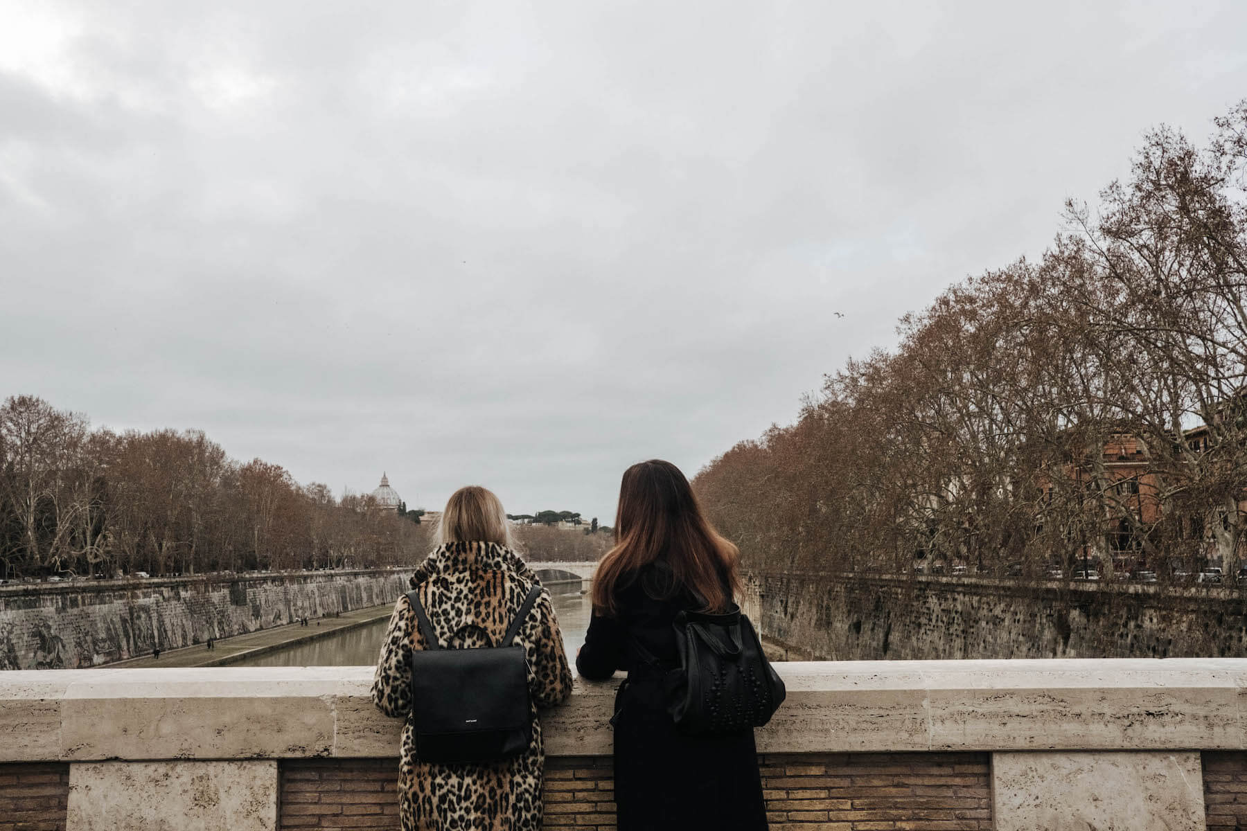 Sisters on a bridge looking out over a river on a family trip in Rome, Italy