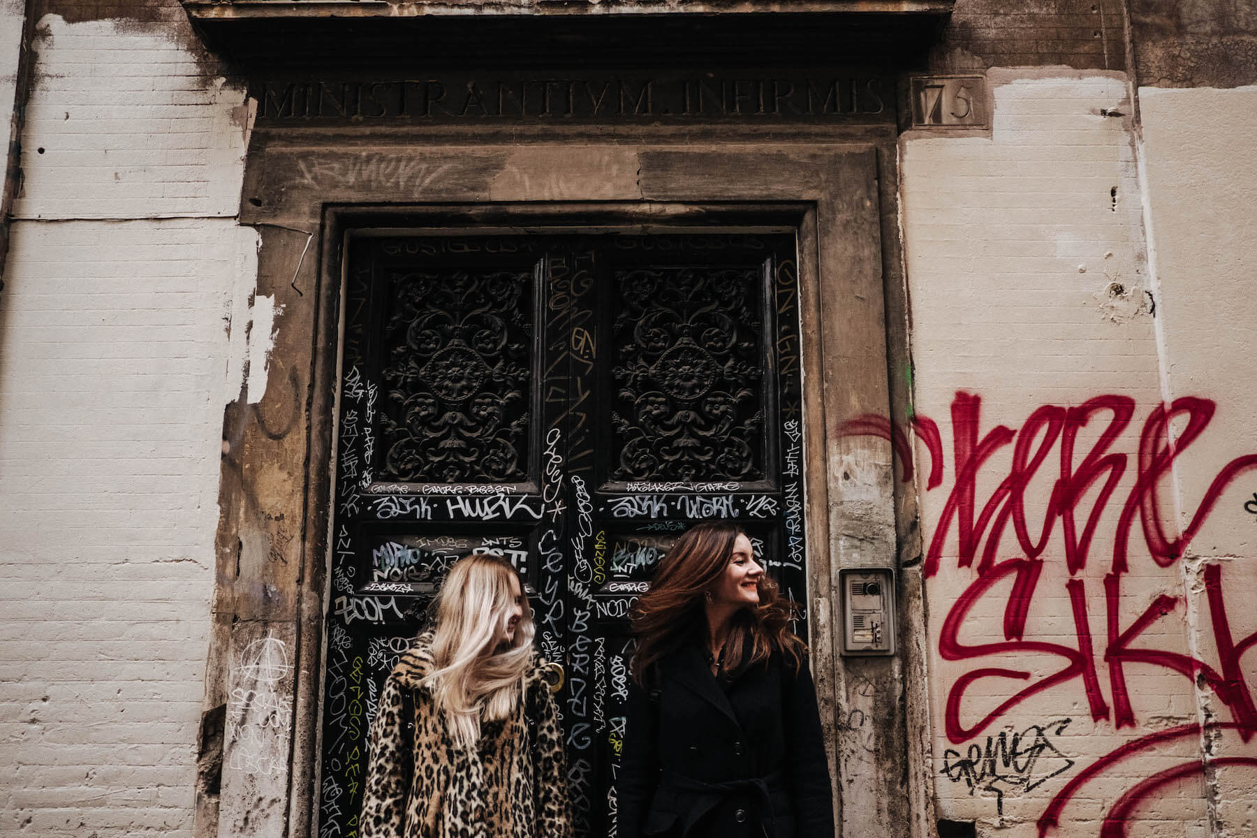Sisters standing against a feature graffitti doorway together on a family trip in Rome, Italy