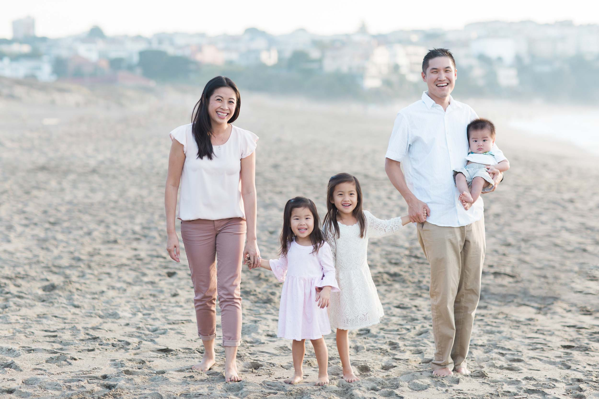 A family smiles and holds hands on a beach in San Francisco.