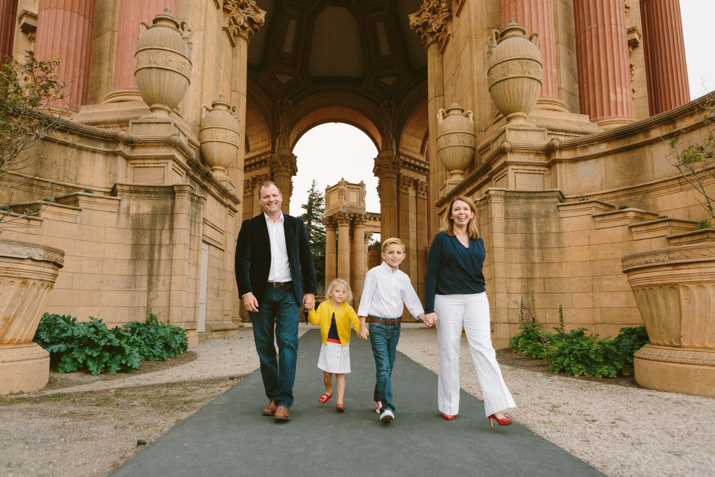 A family of four holds hands and walks near the Palace of Arts in San Francisco.