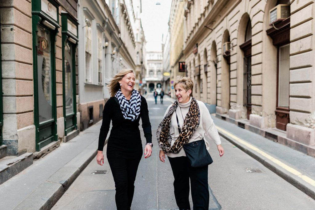 Two women walk down the street laughing in Budapest.