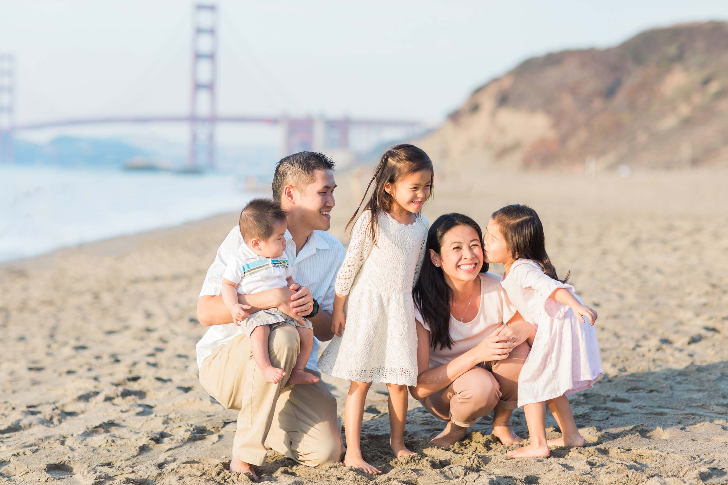 A family smiles at each other on a beach in San Francisco.