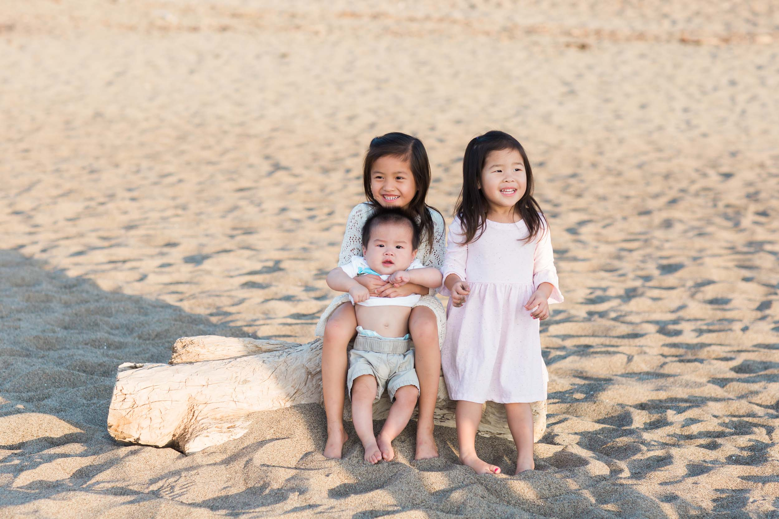 Three children hug and smile on a beach in San Francisco.