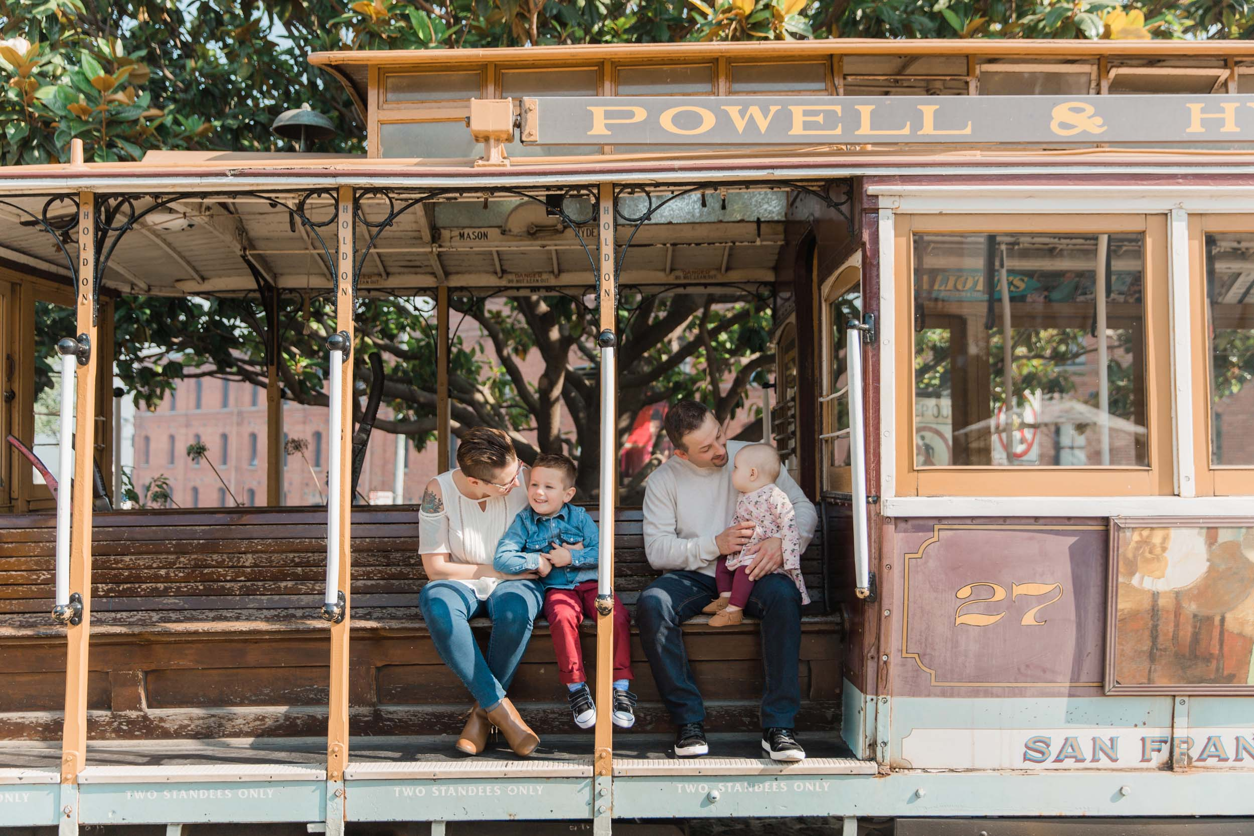A family with two small children sit on a trolley in San Francisco.