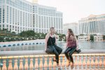 Two friends sit in front of a fountain in Las Vegas.