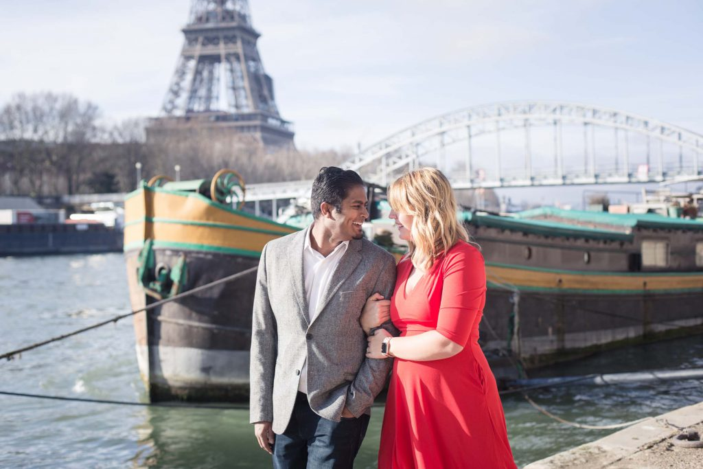 A couple walks arm in arm along the Seine in Paris with the Eiffel Tower in the background.