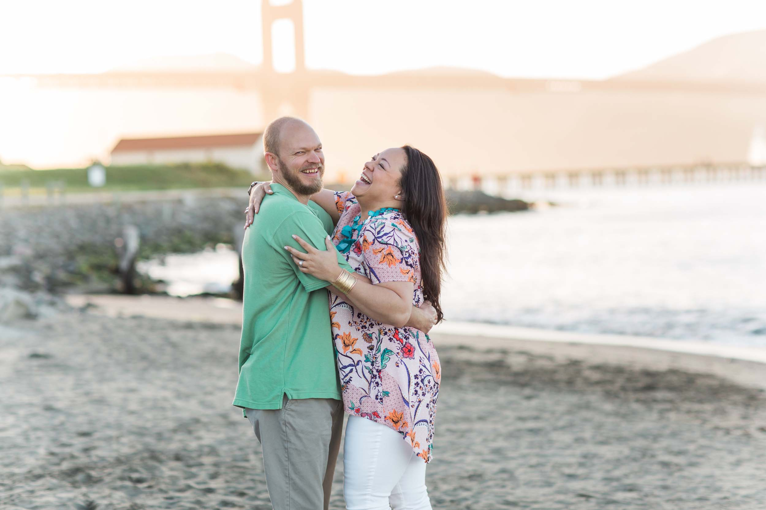 A couple embraces on a beach in San Francisco in front of the Golden Gate Bridge.