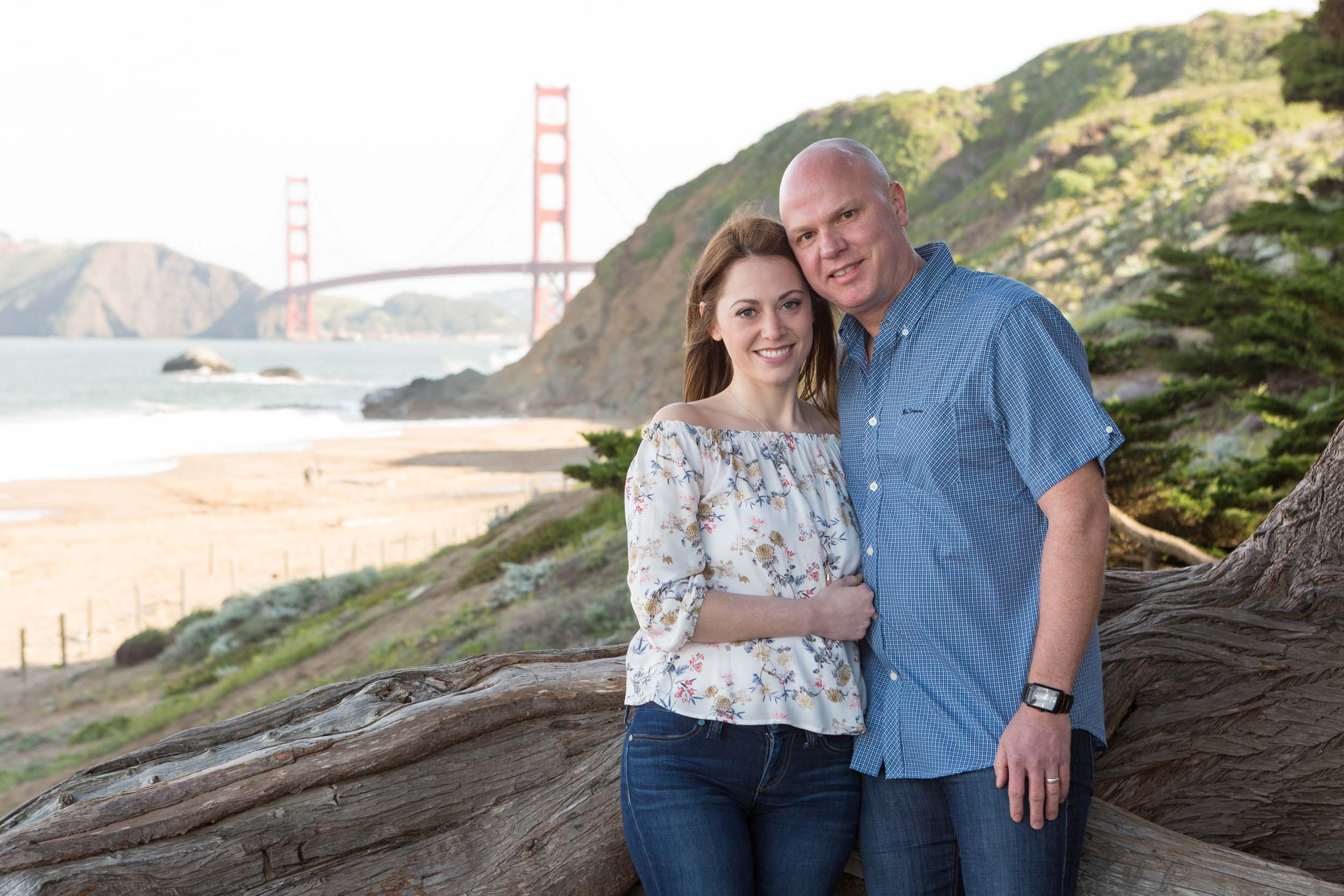 A couple poses on a beach in front of the Golden Gate Bridge in San Francisco.