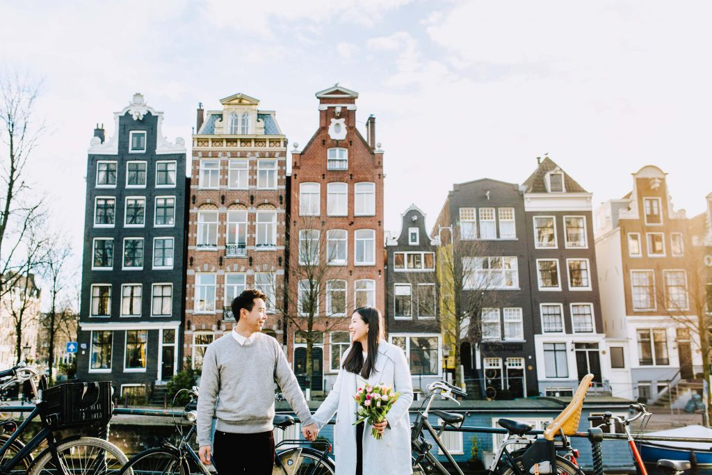 A couple holds hands while the woman holds a bouquet of tulips in Amsterdam.