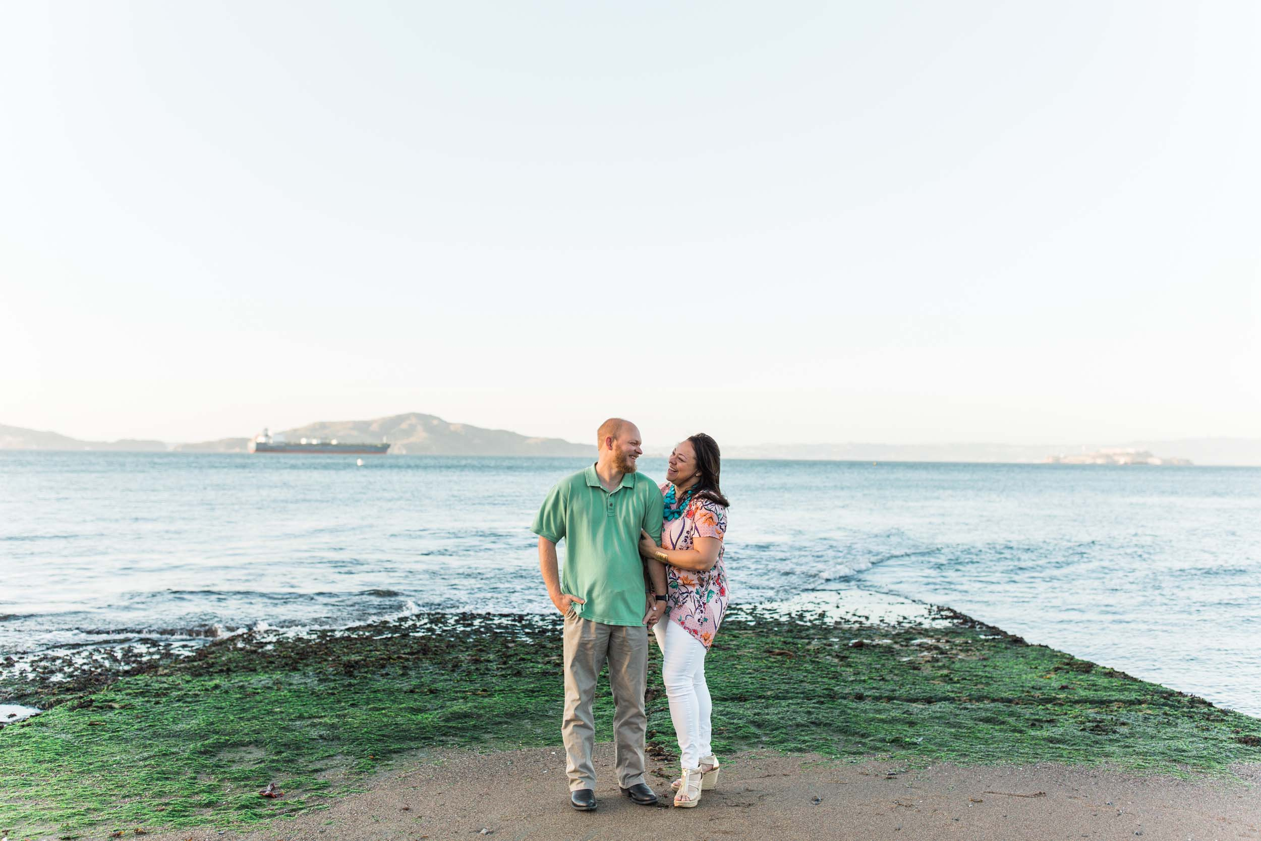 A couple looks at each other and smiles overlooking the water in San Francisco.