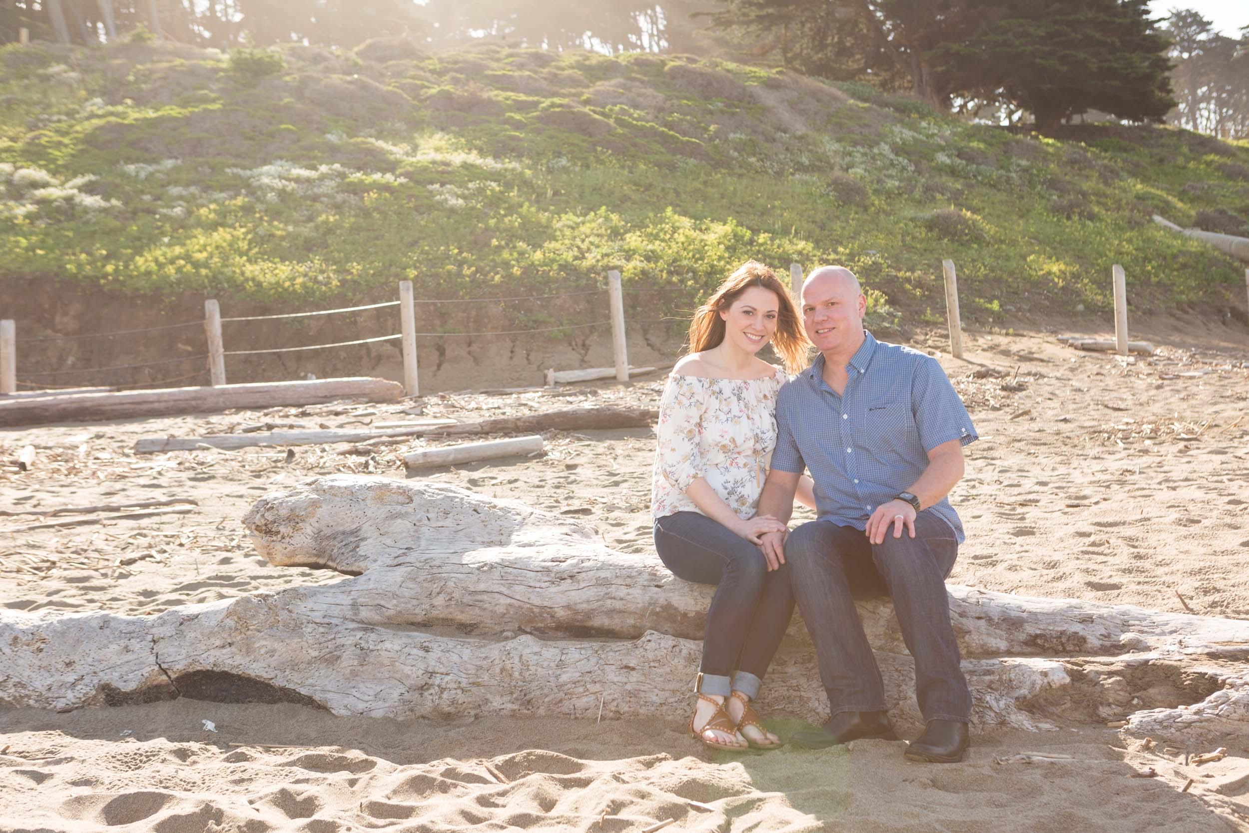 A couple sits on a log and smiles on a beach in San Francisco.