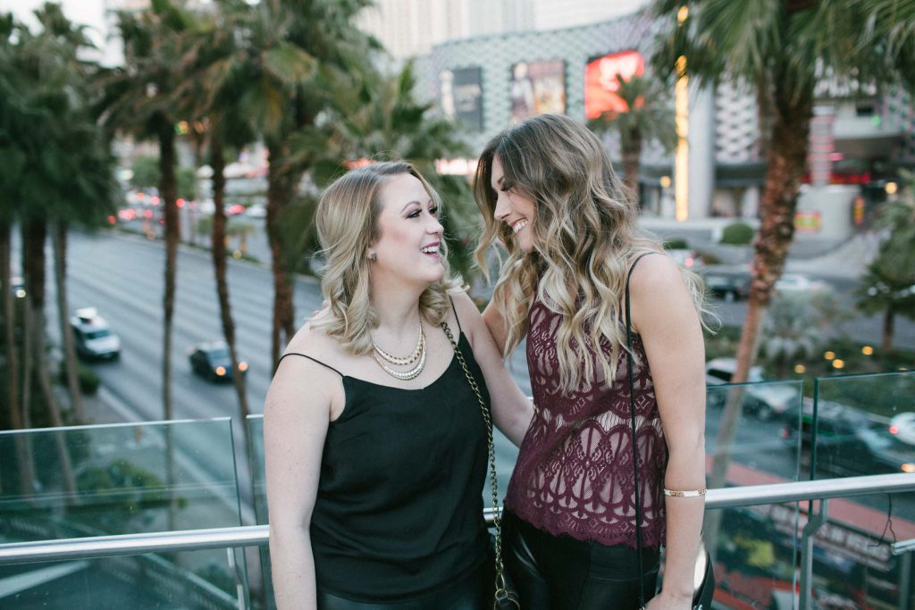 Two girlfriends smiling at each other in Las Vegas
