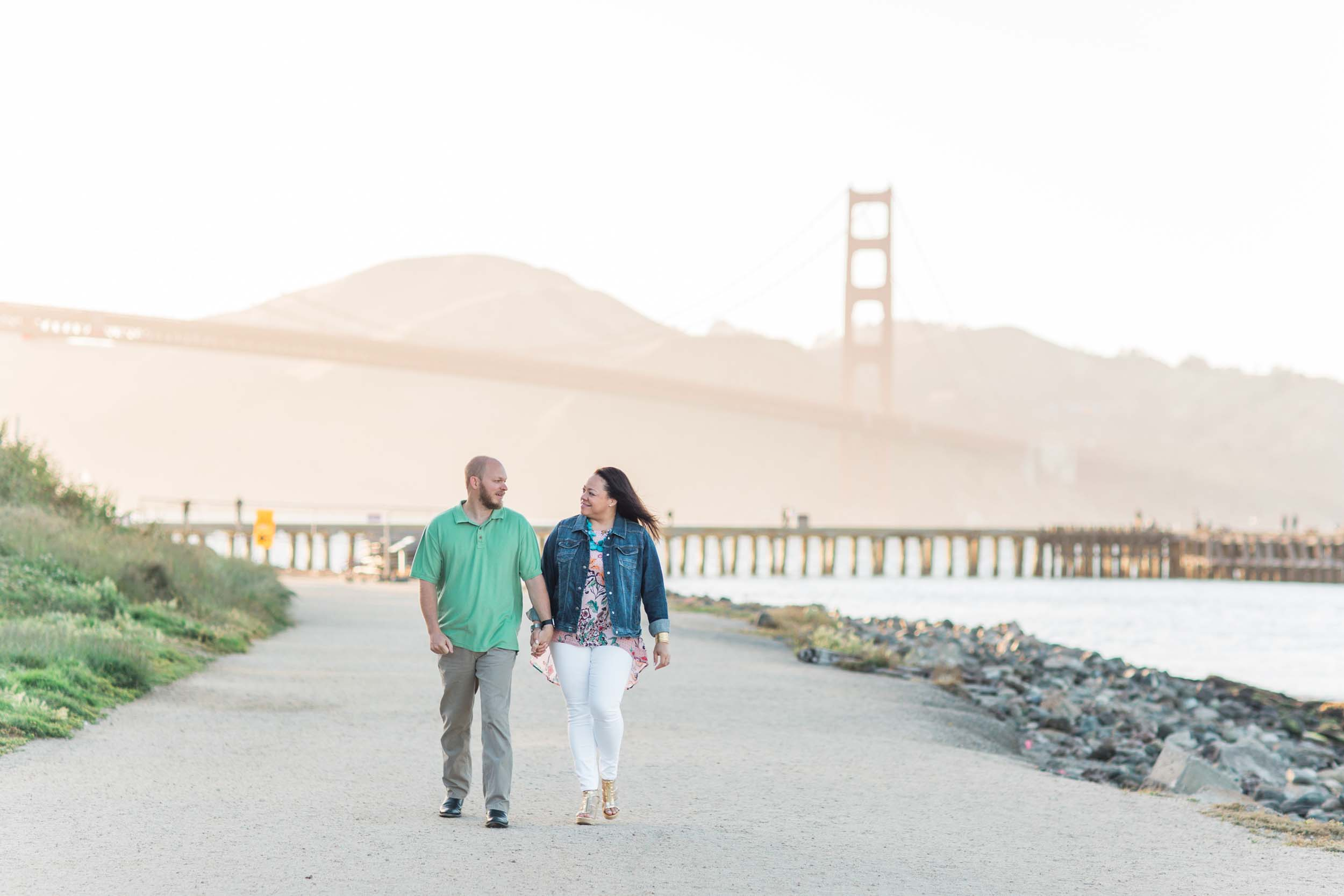 A couple walks along a waterfront path in San Francisco with the Golden Gate Bridge in the background.