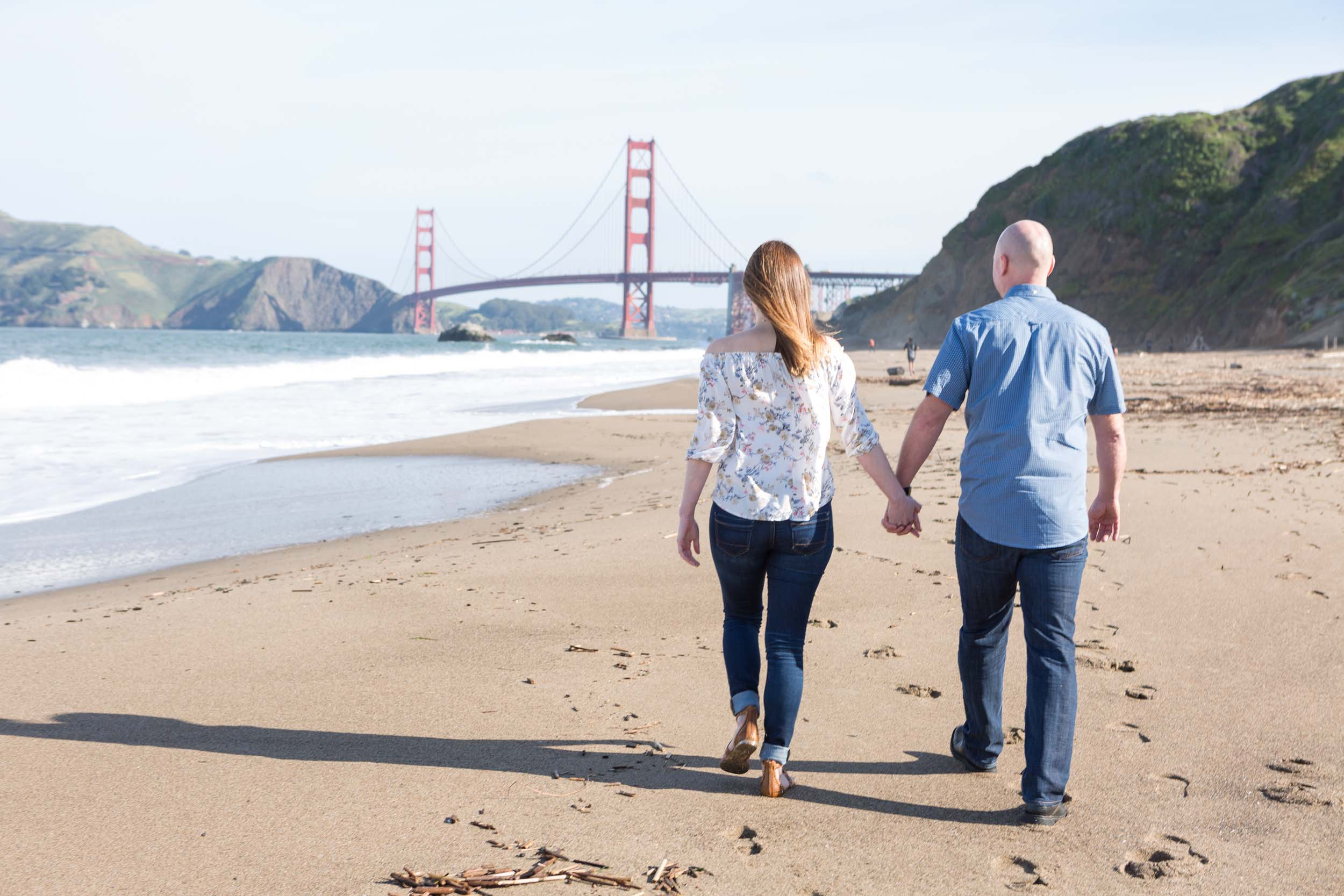 A couple holds hands and walks along the beach with the Golden Gate Bridge in the background in San Francisco.