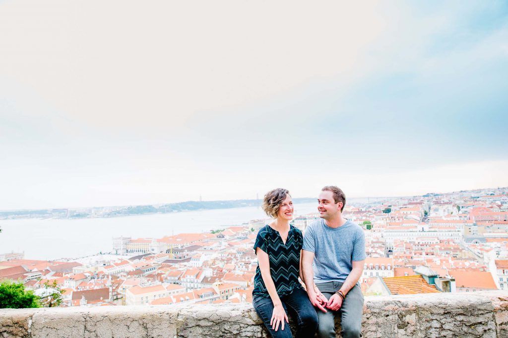 A couple sits on a ledge overlooking a view of Lisbon.