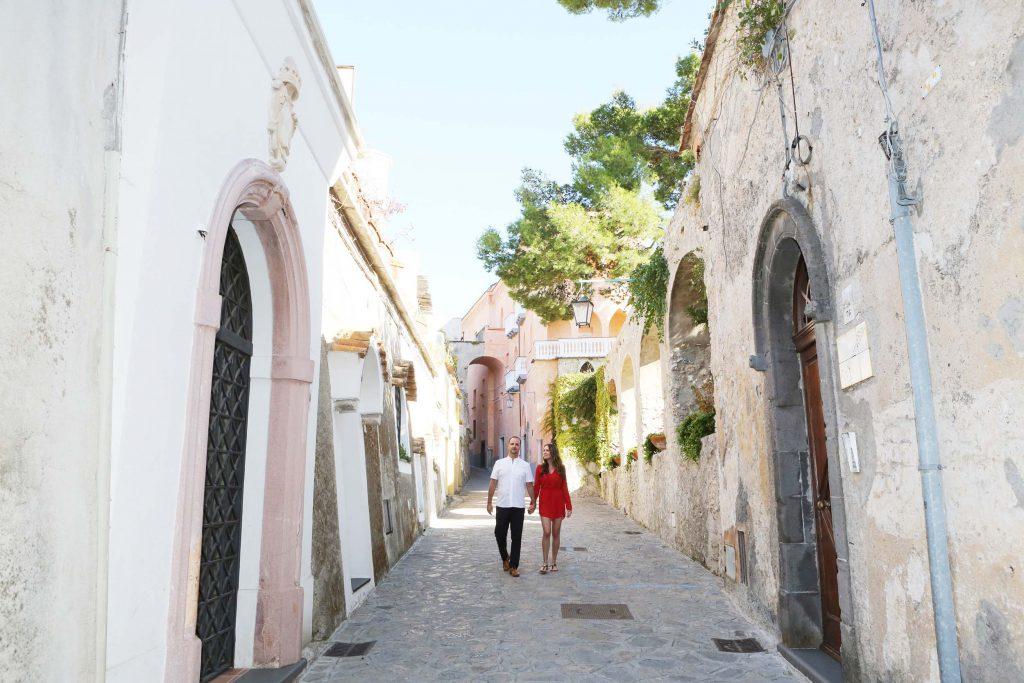 A couple walks down a narrow cobblestone street in the Amalfi Coast.