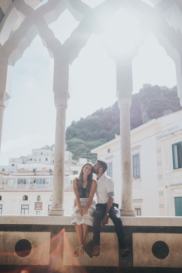 Couple sitting on a wall ledge beneath an archway with the male kissing his female partner's forehead in Amalfi Coast, Italy