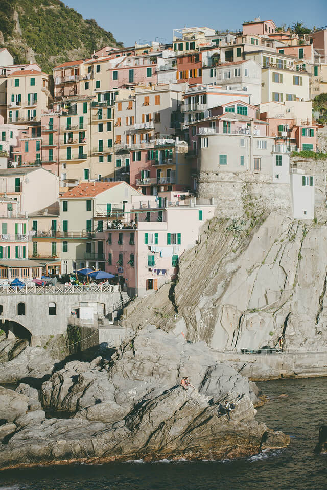 Cinque Terre coastline with colourful houses perched along the cliffs and people sitting on the rocks by the water in Italy