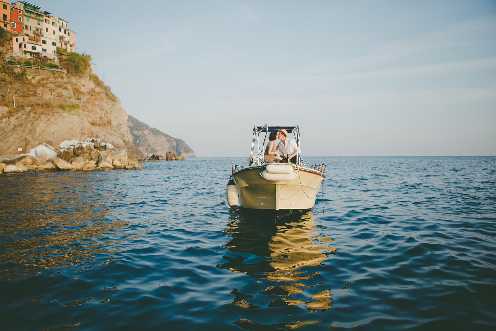 Two people kissing on a small boat in the waters of Cinque Terre, Italy