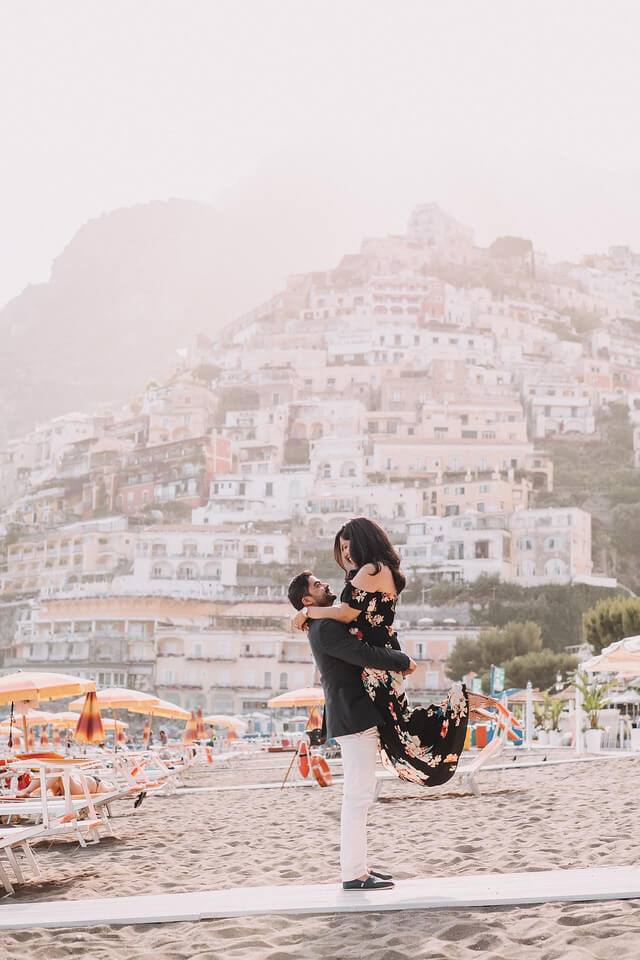Man holding up his female partner on a beach in Amalfi Coast, Italy on a couples trip