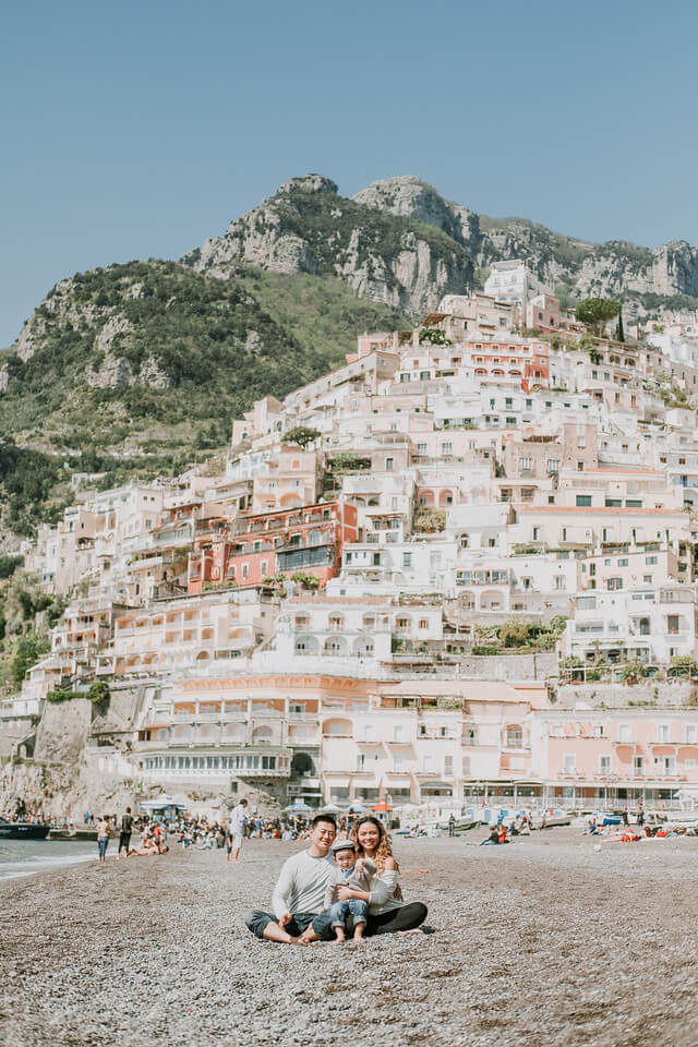 Family sitting on the beach together with the Amalfi Coast pastel pink buildings in the background in Italy