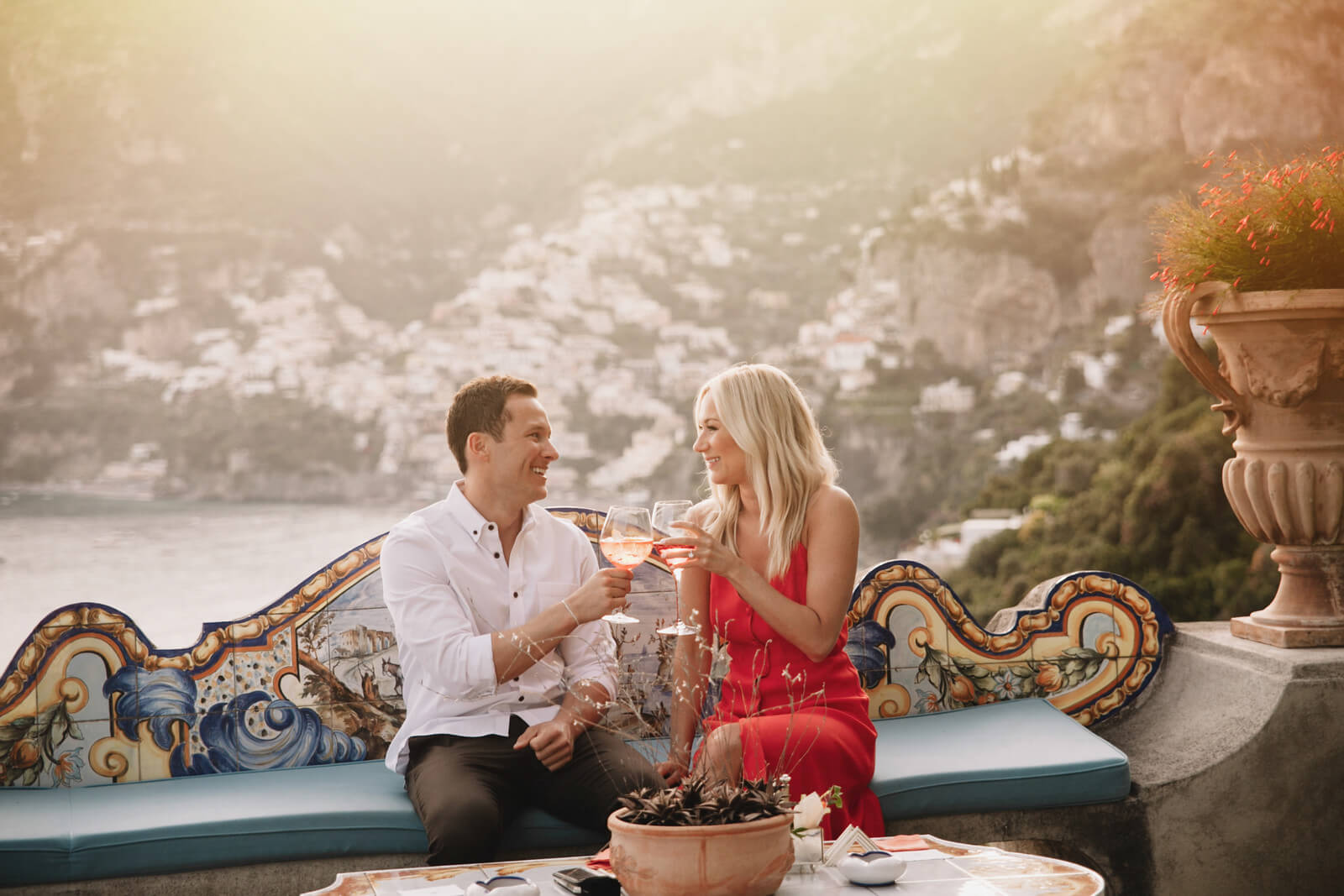 Couple toasting wine glasses together at sunset in Amalfi Coast, Italy