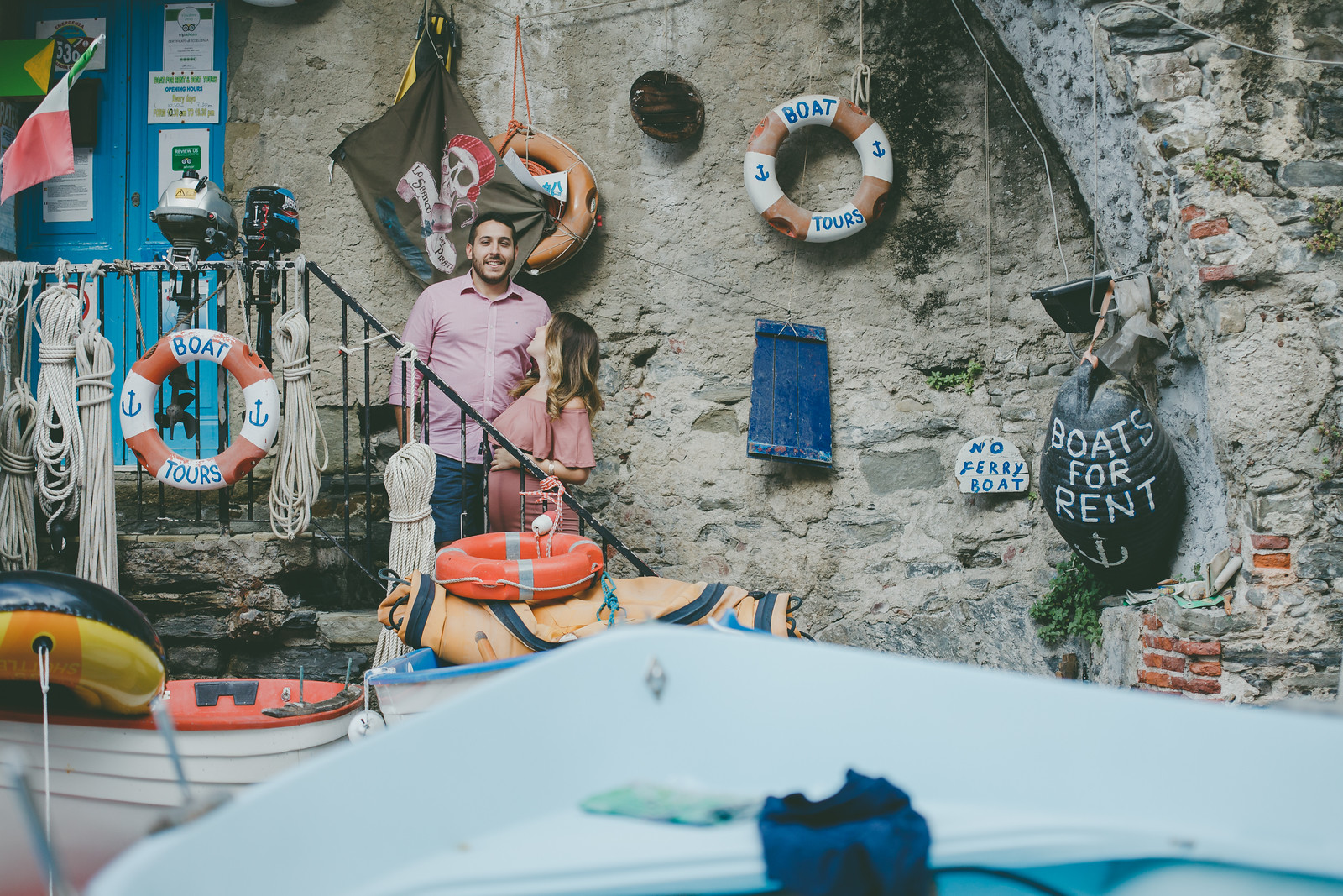 Couple standing on staircase surrounded by fishing materials in Cinque Terre, Italy
