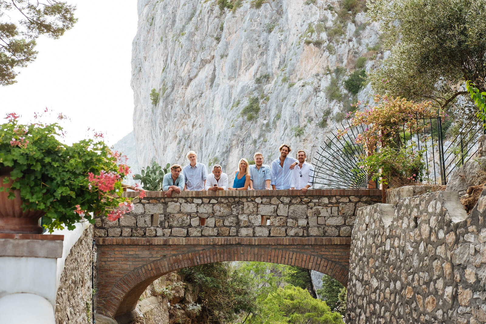 Family of seven standing along a bridge together on a family trip in Amalfi Coast, Italy