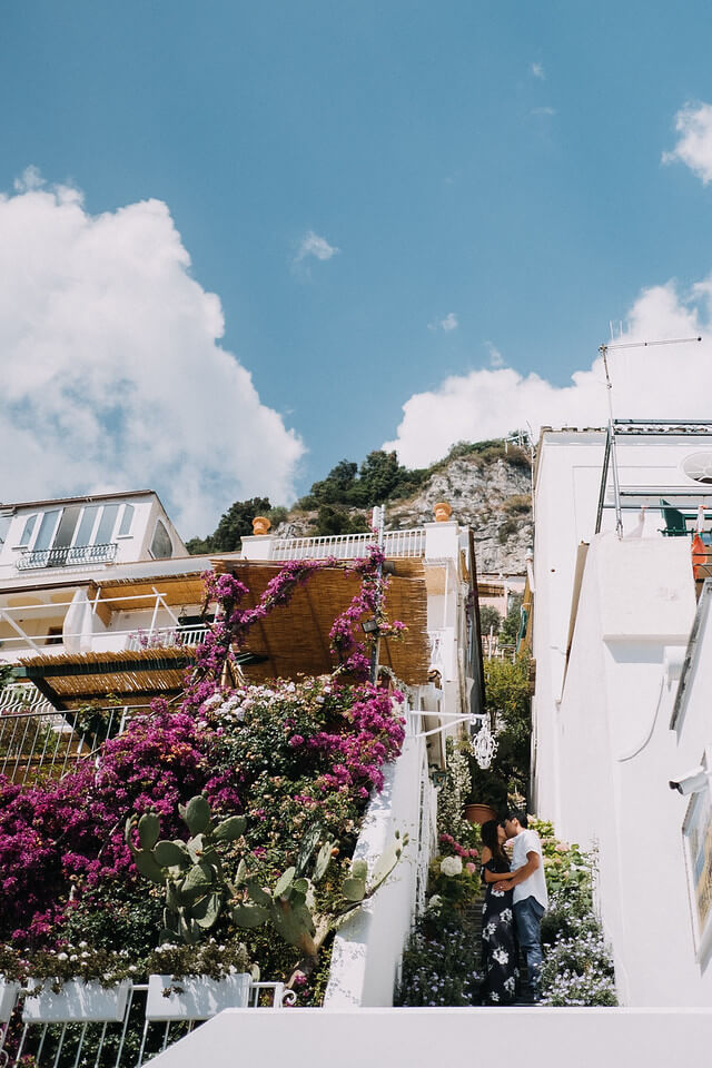 Couple kissing while they hide between two buildings covered in flowers for privacy in Amalfi Coast, Italy