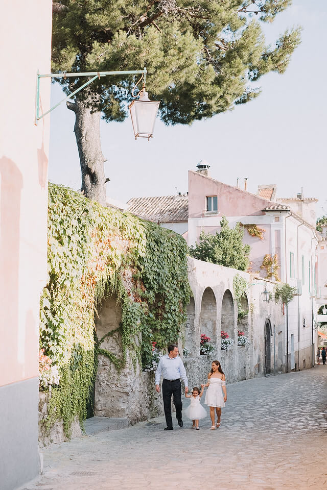 Family of three with an infant daughter walking along a cobblestone pathway in Amalfi Coast, Italy