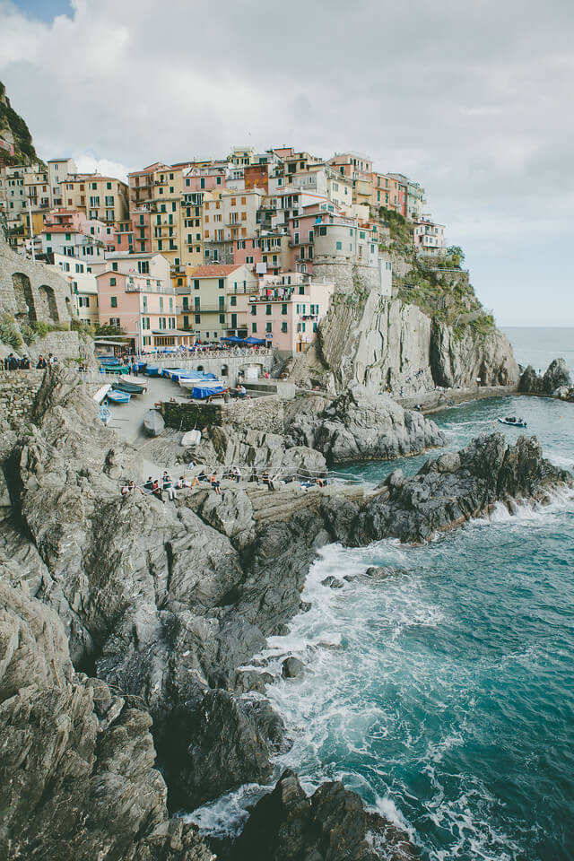 Cinque Terre coastline in Italy with a group of people sitting along the rocky shoreline