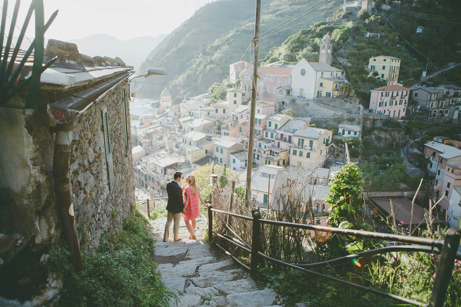 Couple holding hands and walking down stairway in Cinque Terre, Italy