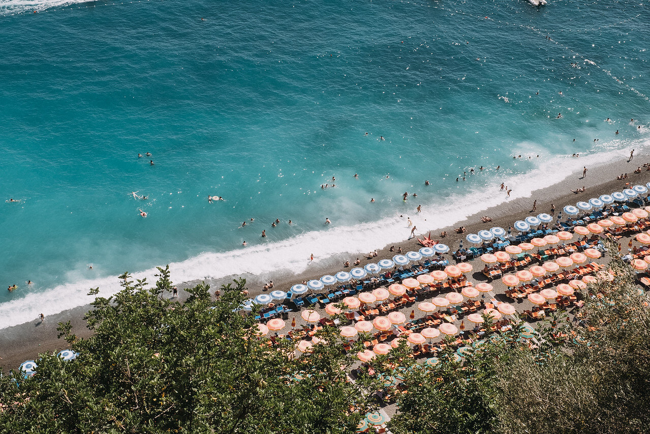 Many people swimming in the water and suntanning at Spiaggia di Laurito beach in Amalfi Coast, Italy