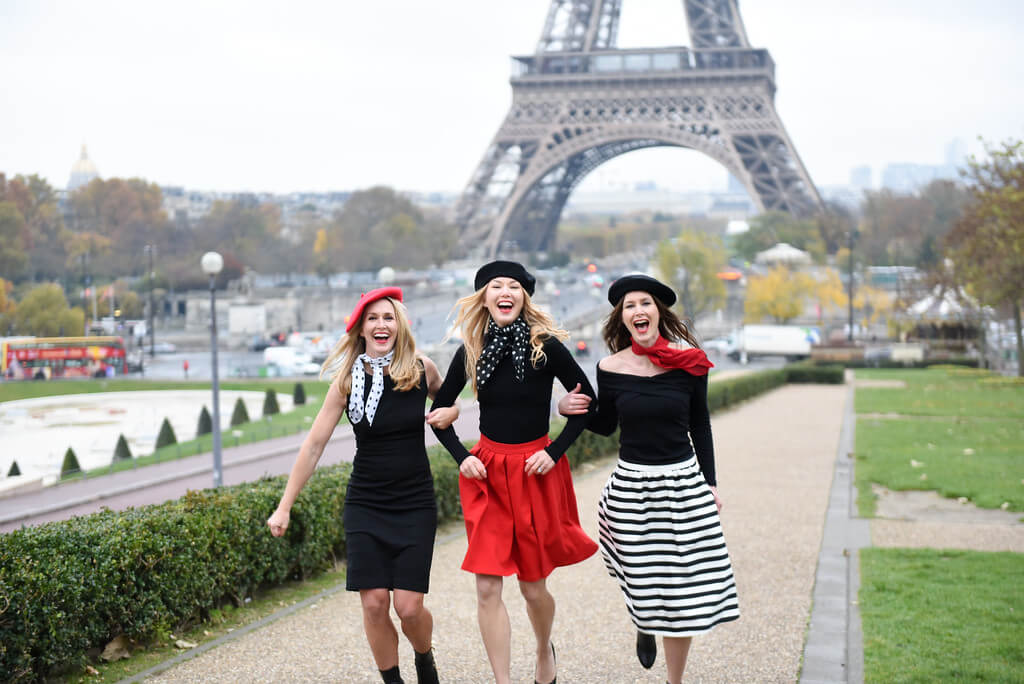 Friends wearing skirts and stripes running in front of Eiffel tower in Paris, France