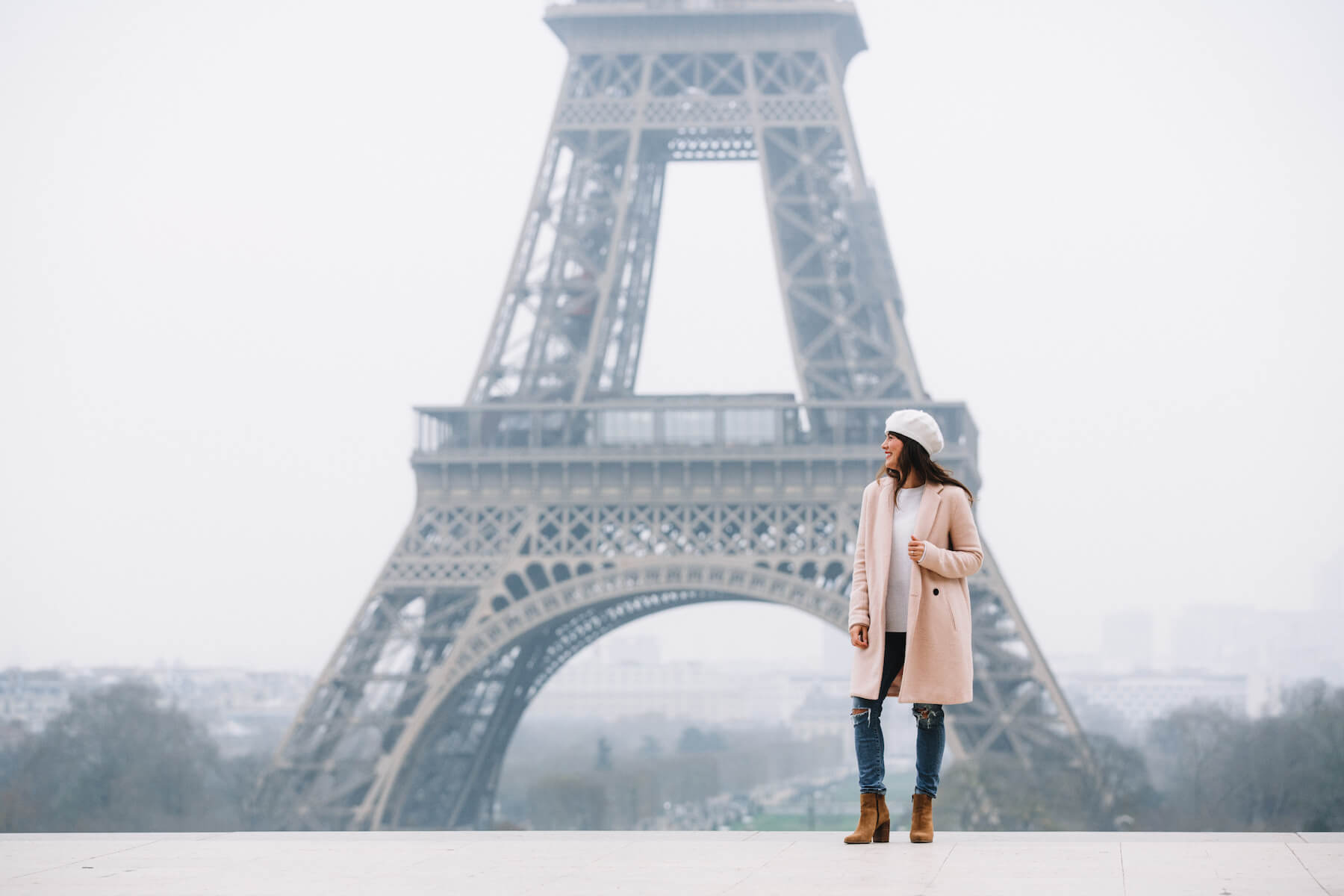 Woman smiling with the Eiffel Tower in the background on a solo photo shoot in Paris, France