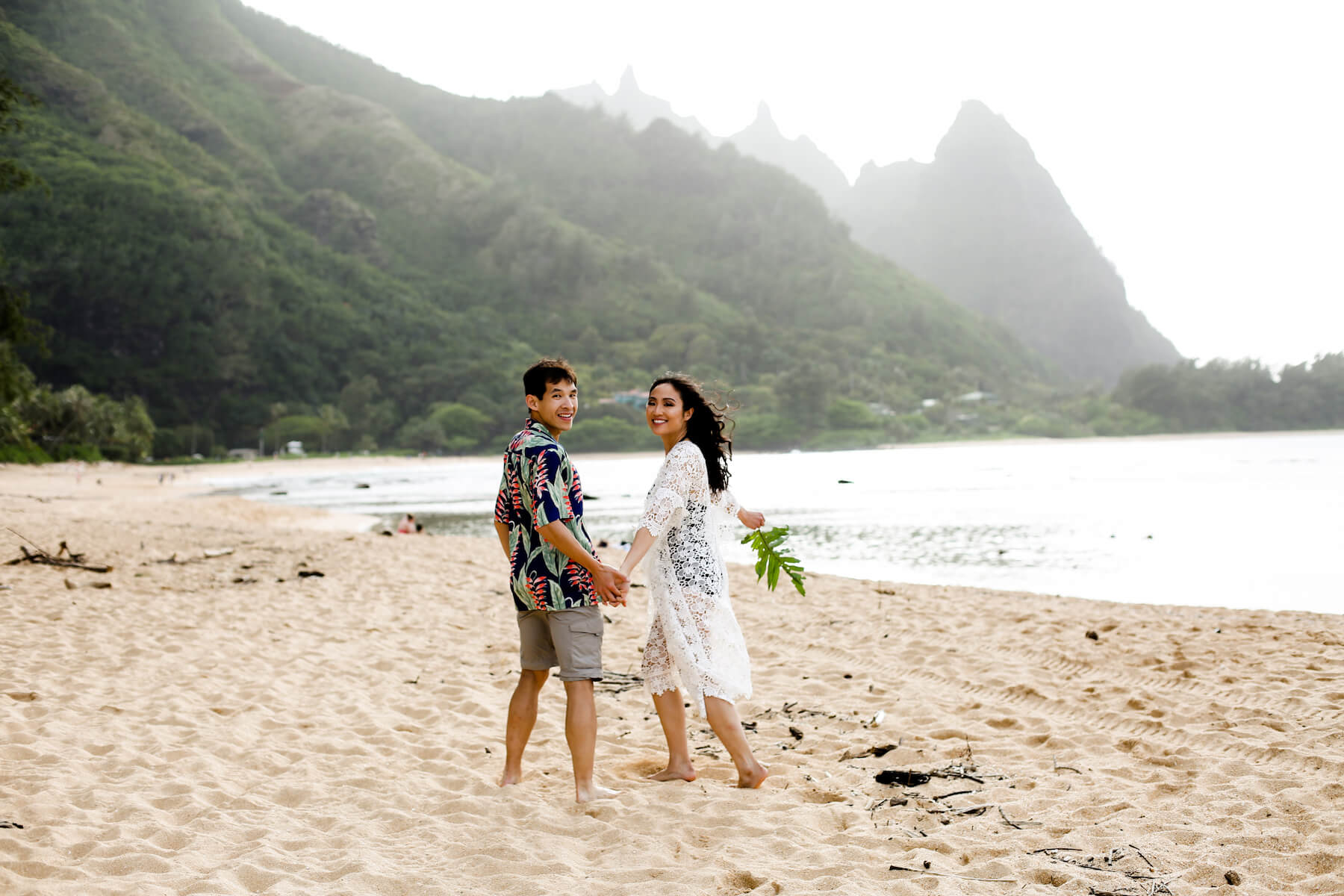 Couple holding hands and looking back on a beach in Kauai, Hawaii