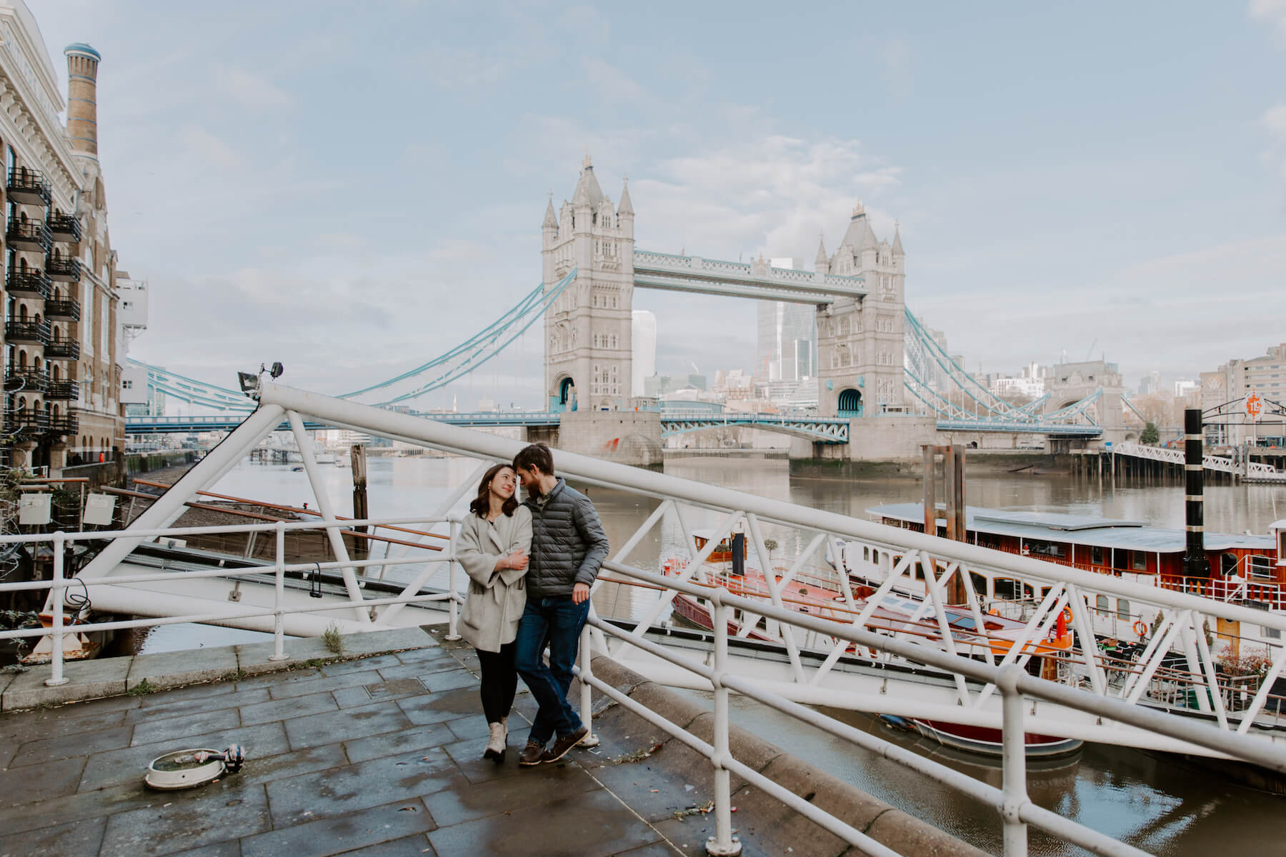 A couple hugging in front of the Tower Bridge in London on a couple photoshoot with Flytographer.