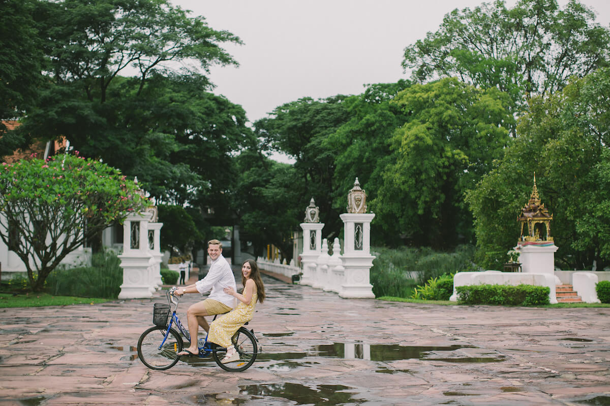 Couple riding a bicycle in Chiang Mai, Thailand on a photo shoot with Flytographer
