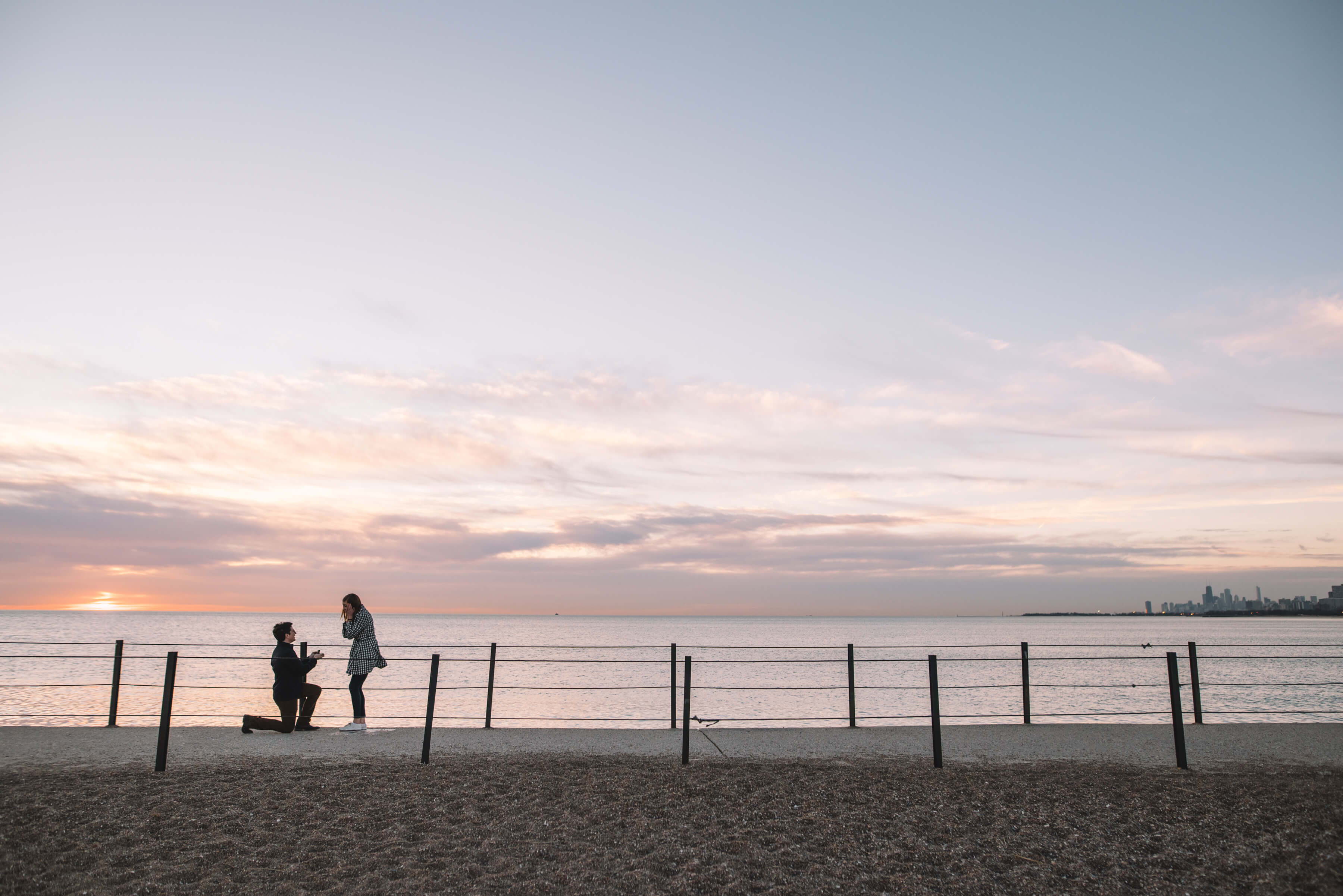 Man proposing to his partner at sunset with the ocean and downtown Chicago in the background