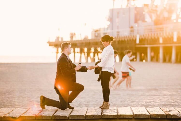 Man proposing to his partner along a boardwalk in Los Angeles, California USA