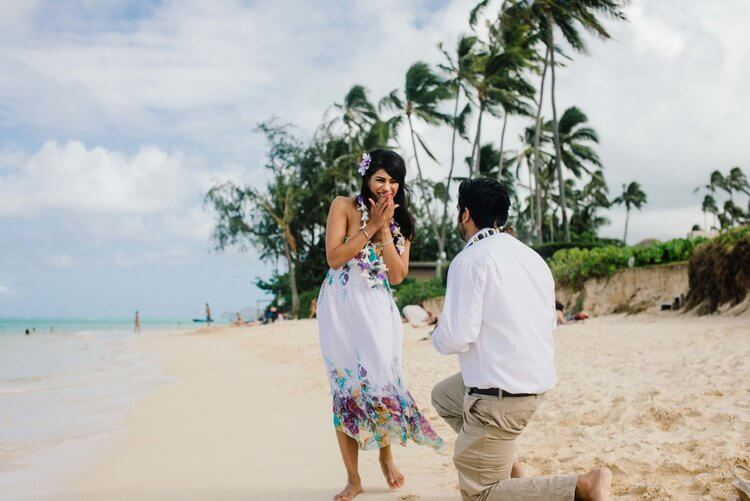 Woman shocked and happy at her partner's surprise proposal on a beach in Honolulu, Hawaii USA