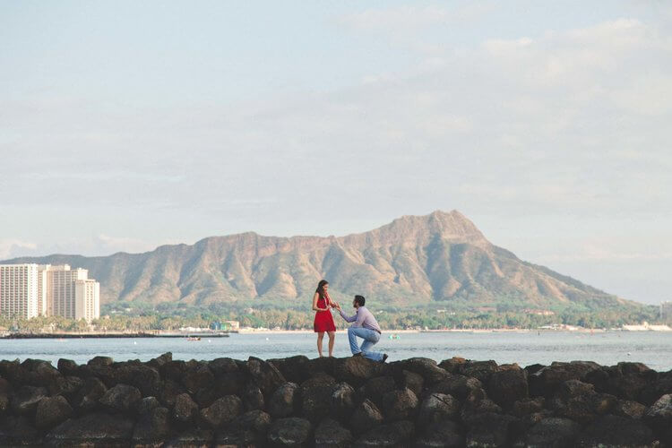 Woman shocked and happy at her partner's surprise proposal at Waikiki Beach Rock Wall in Honolulu, Hawaii USA